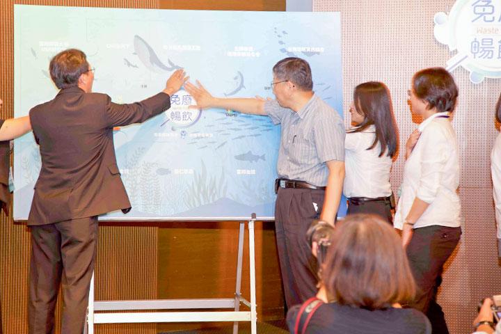 慈心有機農業發展基金會執行長蘇慕容(左)與臺北市長柯文哲以拼圖儀式共同呼籲「用愛環抱海洋 支持免廢暢飲」行動