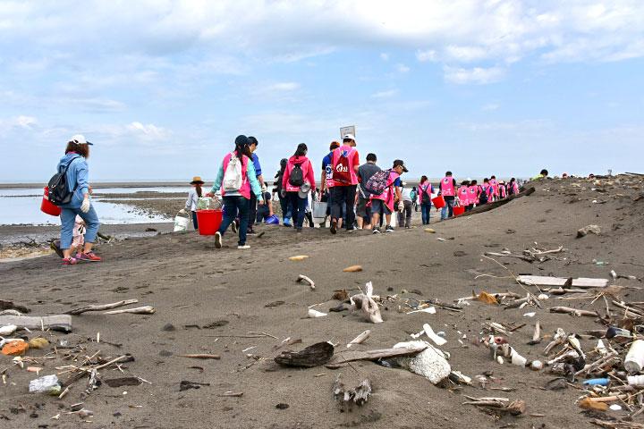 企業員工分組前往充滿垃圾的海岸準備淨灘