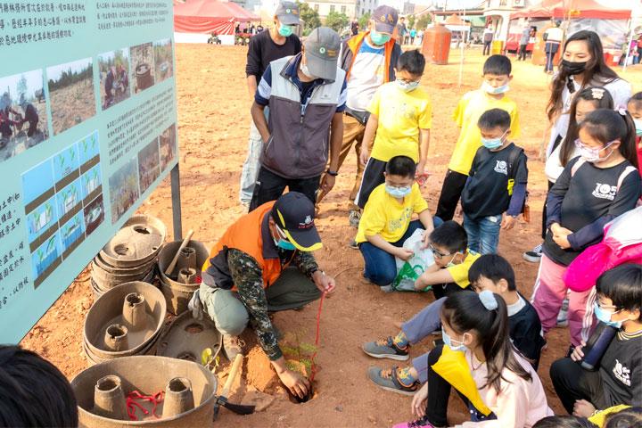 慈心、金門縣政府於植樹節種樹活動前,先教導學童了解水寶盆原理、安裝技巧。(金門縣林務所提供)