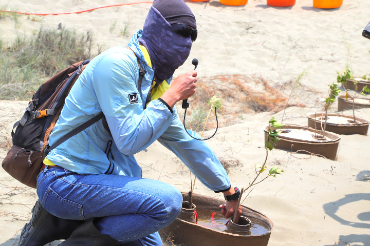 慈心基金會種樹專員劉建福示範將水寶盆儲滿水,可供樹苗吸收一個月