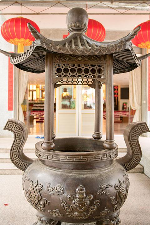 主殿正門不若側門顯眼氣派,卻有雕著八吉祥的攢尖頂香爐相伴。