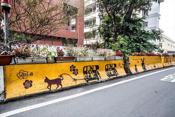 夫妻倆帶著兒女和兒女的同學,彩繪故事館對面的水泥護欄。